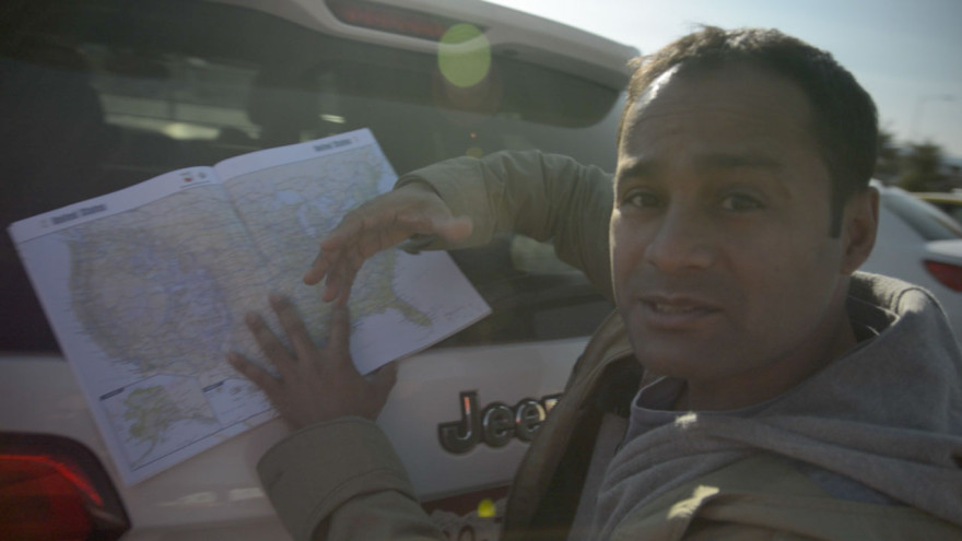 Alom leans on the car to explain our route across the US.